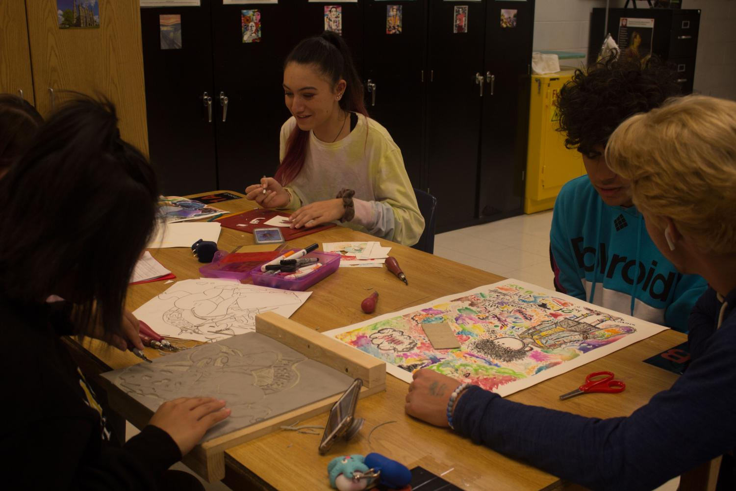 Students finish and discuss art projects.