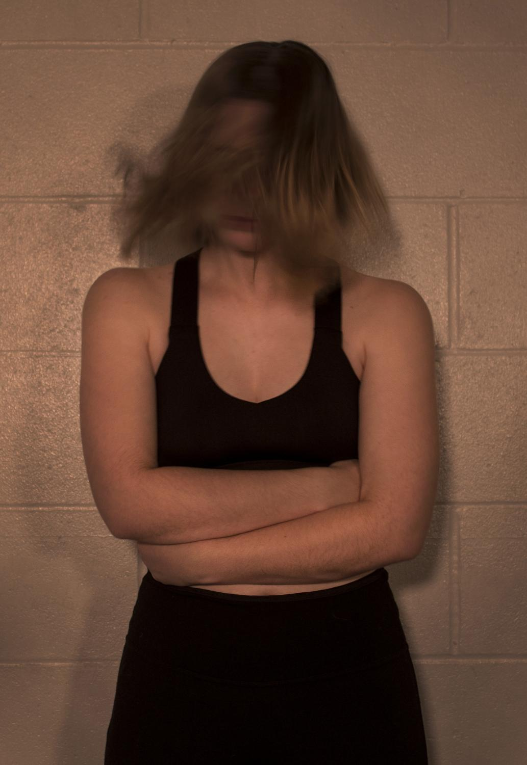 Lanie Sanders thrashes her head back and forth, portraying the anxiety inflicted by her eating disorder.