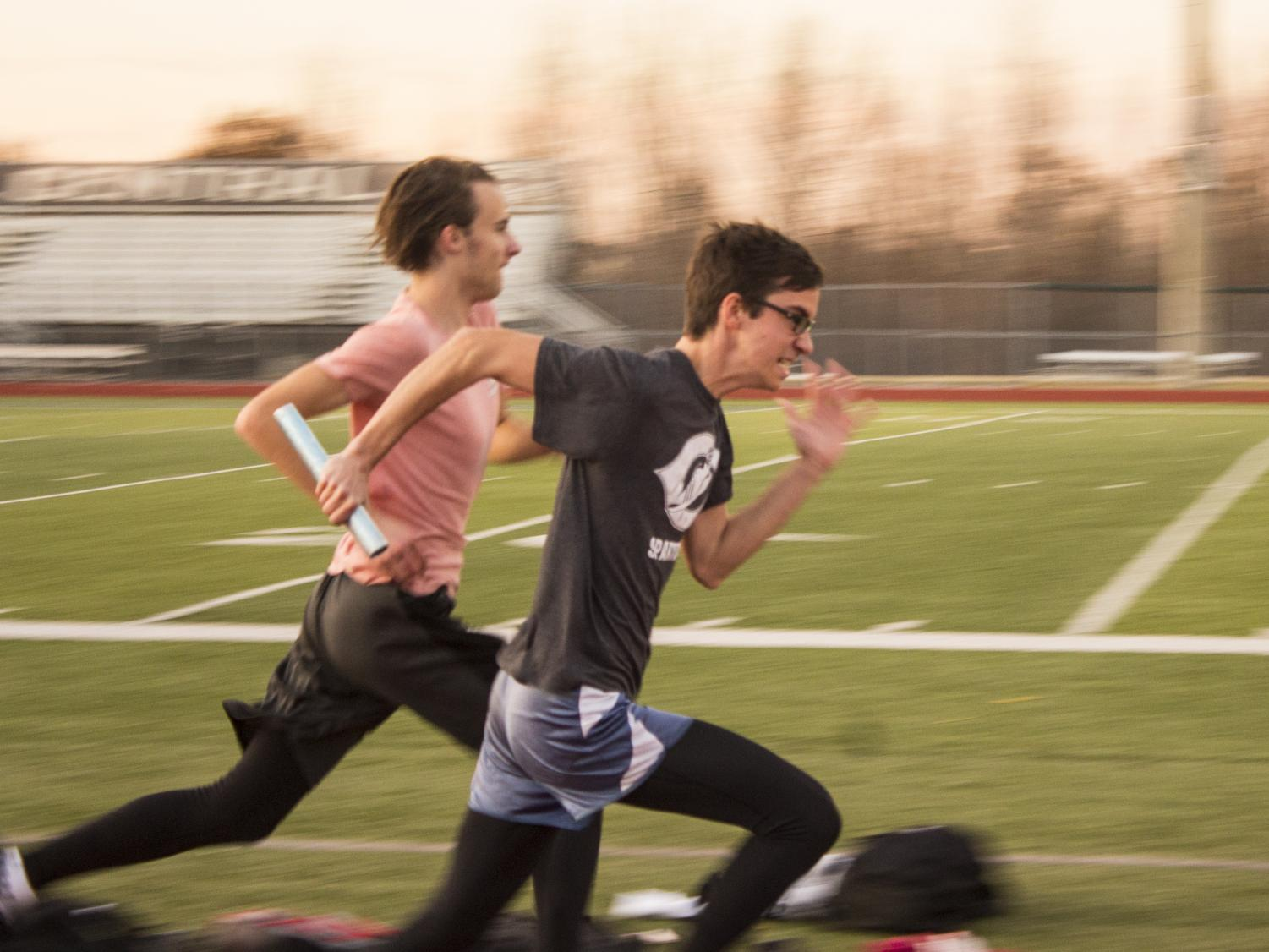 "OFF-SEASON SPRINTING: Eli Allen and Reed Easterling perform handoffs with a baton. ""My biggest goal is just to stay in shape and to get myself better so that during track season I can get better and better times,"" Easterling said."