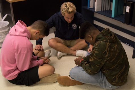 Senior Allen Butterfield prays over freshman Lucas Schuster and junior Tyler Hoskins. This particular meeting was all about being there for your friends and supporting them. The participants met in small groups and poured their hearts out. They shared their struggles, their praises, and their love for the Lord.