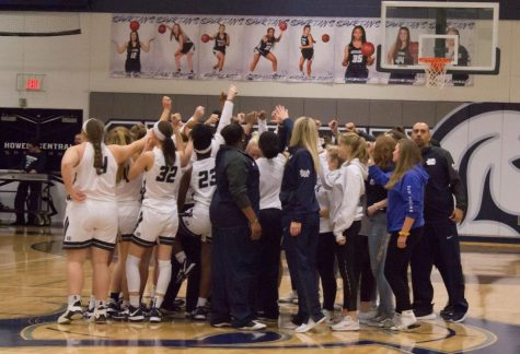 The girls basketball team celebrates a win at center circle after defeating GAC South opponent Troy Buchanan High School. The team improved to 12-0 after this win.
