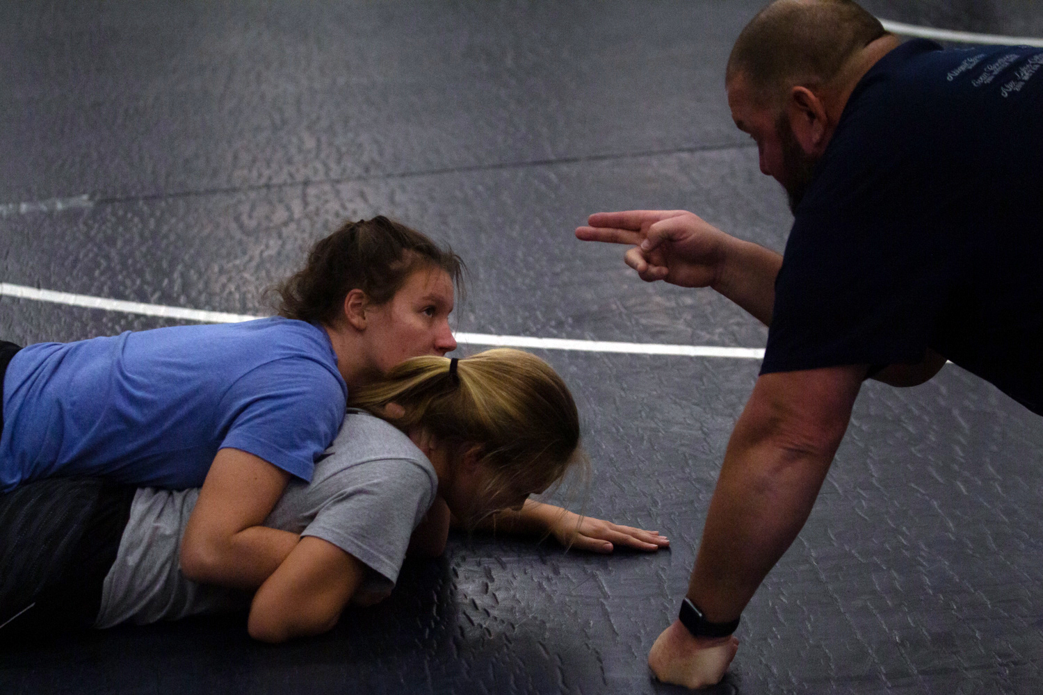 Coach Kurt Kruse directs junior Rhyen Standridge on how to properly execute a half-nelson on Mary Kate Neal. Practicing challenges at practice improve their performance at meets.