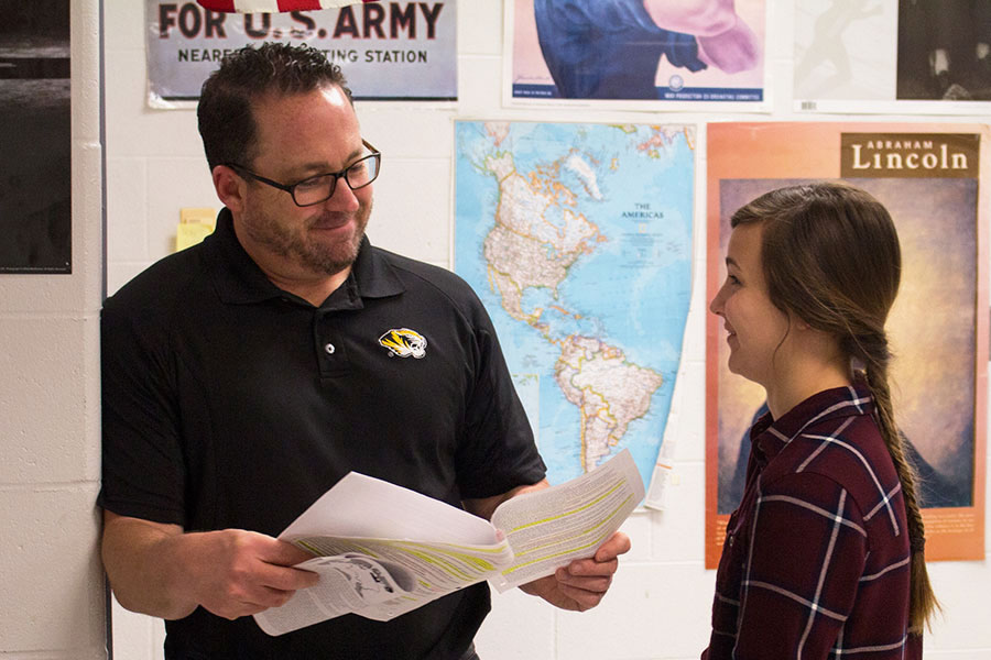 Mr. Lober looks over class material smiling as he helps a student with her questions. Mr. Lober teaches AP European history; a course with a heavy memorization workload.