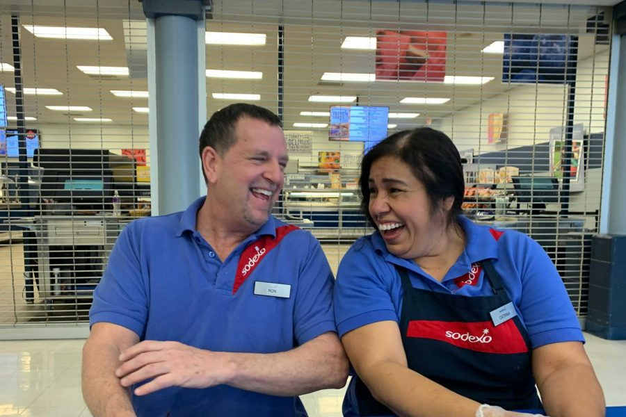 Cafe staff members Ron and Catrina laugh in the cafeteria. They aim to bring joy to students each day.