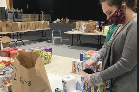 A volunteer is pictured packing food into grocery bags to go to a
