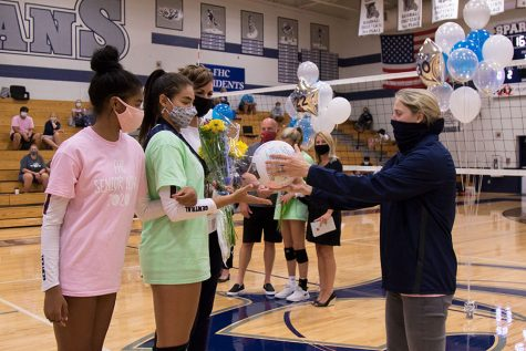 Elexus Pearson reaches out to receive a signed volleyball from Coach Gronek.