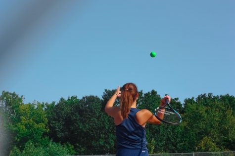 Libby Mathis practices serving before taking her real swing.