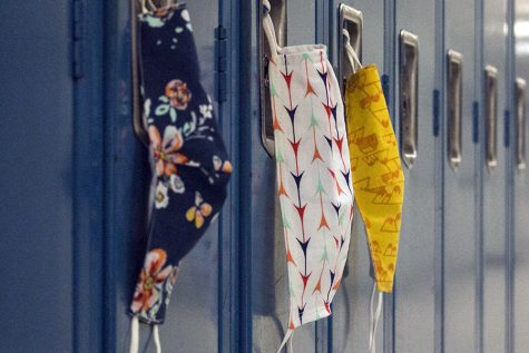 Face masks hang from lockers in the hallways. Masks are the primary way to stop the spread of COVID-19, but when there are positives, it