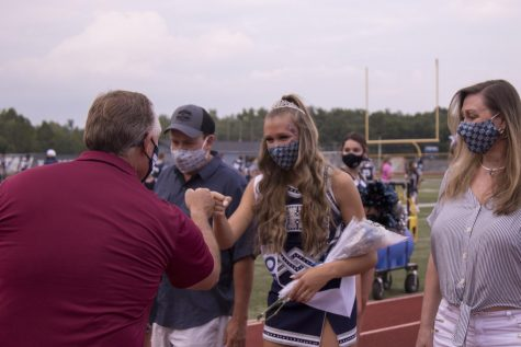 Senior Shaffer Brown fist bumps Dr. Arnel at Senior Night upon receiving her award. Precautions such as mask-wearing have been taken to keep students, coaches, and spectators at sporting events safe.