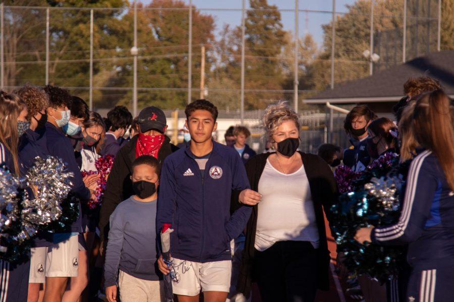 Captain Jimmy Sanchez walks alongside his family during the senior night ceremony.