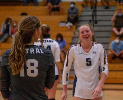 Senior Emma Hultz smiles after a a successful play with her libero, despite the fact that the ladies lost this game 3-1.