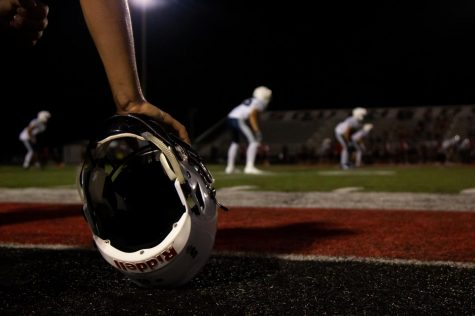 A football player crouches next to his helmet as he prepares for the game.