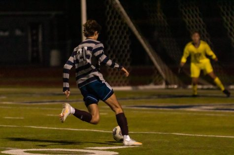 Junior Josiah Gould dribbles before scoring a goal at a previous game. Gould achieved a hat trick at the Oct. 13 game.