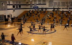 The Varsity Cheerleaders perform at the schools first ever virtual pep assembly while the band and color guard attentively watch on Sept. 23. The gym seemed empty as masked band members social distanced, using up all of the space in the  bleachers. The event was live-streamed into classrooms so they could participate in the spirit week event.