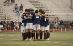 The varsity boys soccer team huddles at a previous game. The players believe that their connection as a team was what brought them so far.