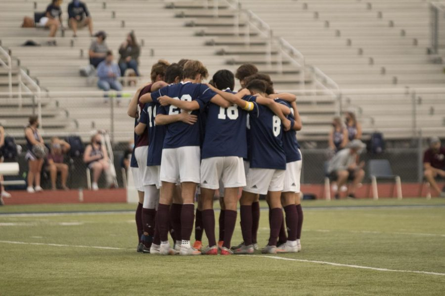 The+varsity+boys+soccer+team+huddles+at+a+previous+game.+The+players+believe+that+their+connection+as+a+team+was+what+brought+them+so+far.