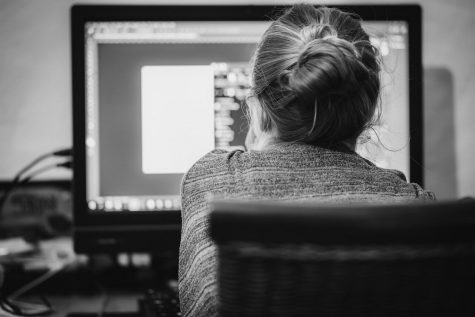 A woman stares at a screen in monochromatic shades. As technology grows more important in our daily lives, it becomes harder and harder to find life outside of its addictive grasp.