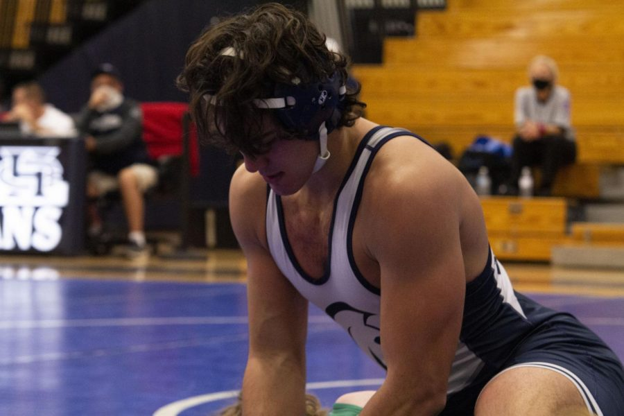 Alex Vogel wrestling on the mat and holding his opponent down.