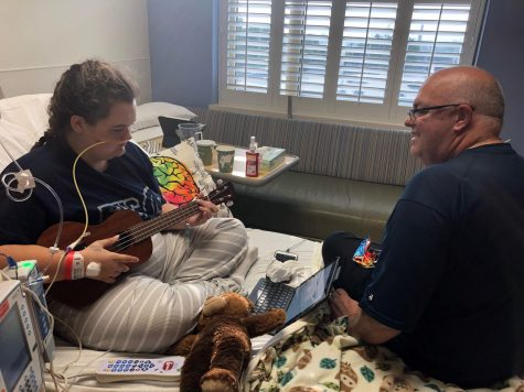 "One of the ways Analiesa Hollowood passed nearly two months in the hospital was by learning some new skills. Here, she plays ""Somewhere Over the Rainbow,"" on the ukulele for her father, Jay. Photo Courtesy of Darla Hollowood"
