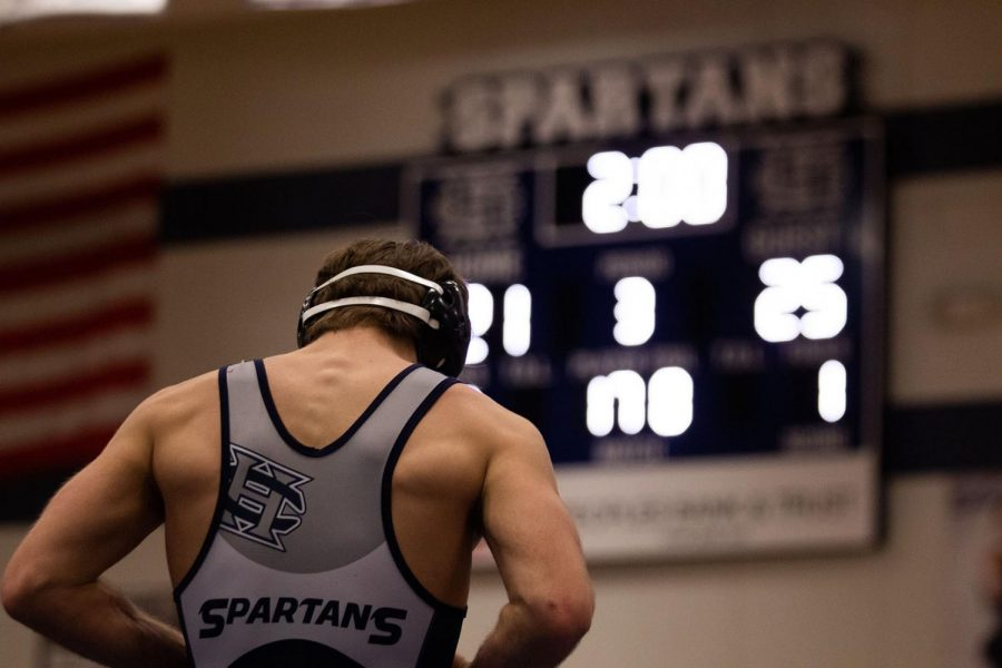 Senior Kaden Hart, with his back to the camera, faces the scoreboard after a match.