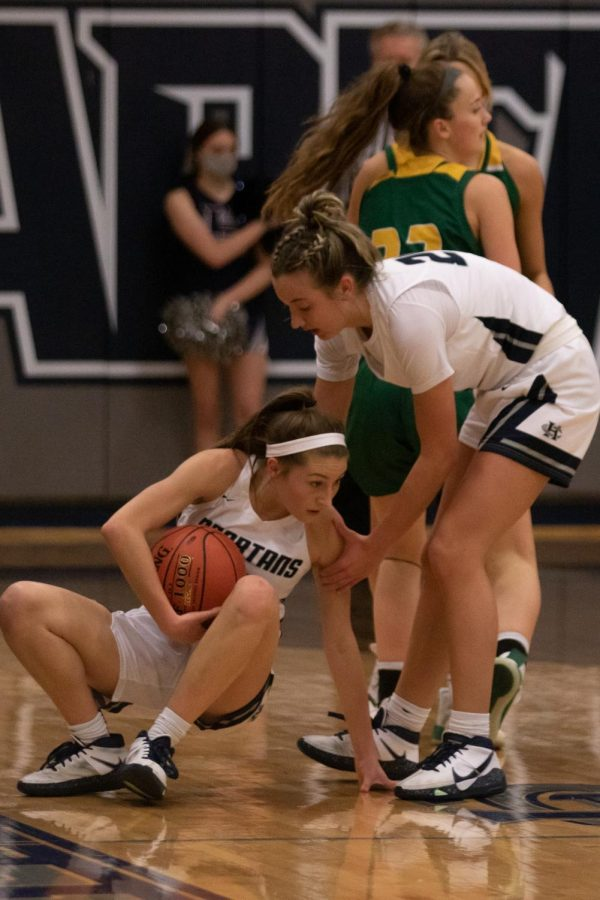 Rylee Denbow reaches to help teammate Gracie Stugart off the ground.