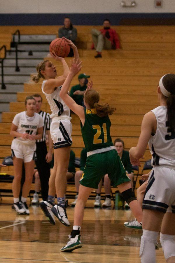 Sophia Tweedie jumps above her opponent to shoot.