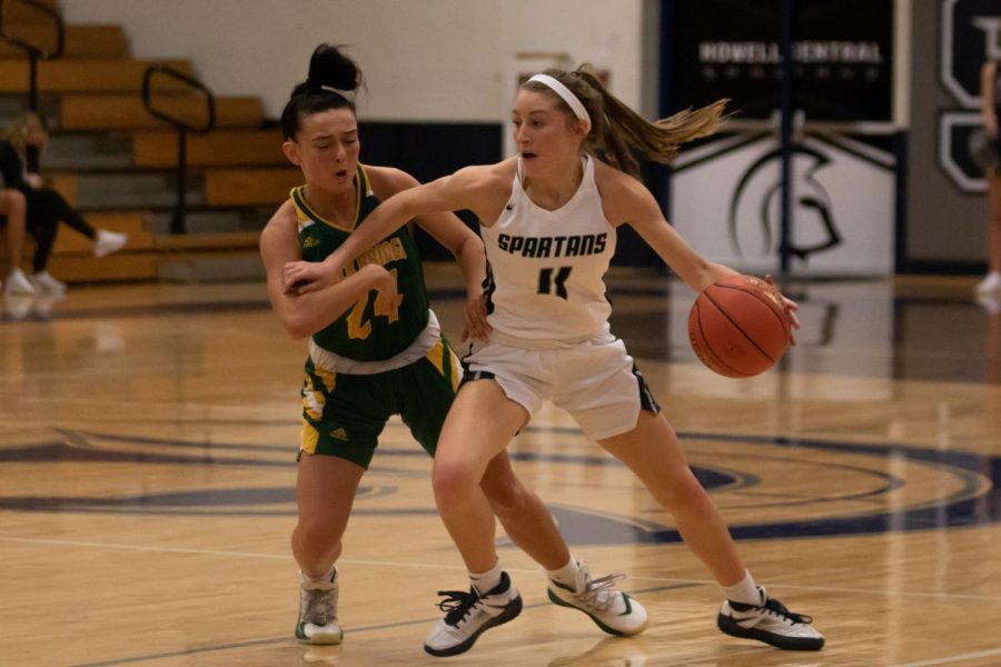 Gracie Stugart pushes past an opposing player as she dribbles towards the basket.