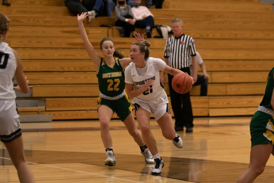 Rylee Denbow dribbles past an opponent with her eyes on the basket.