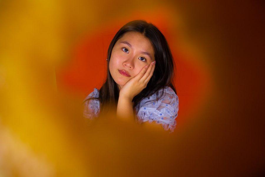 Orange themed portrait of junior, Sydney Tran.