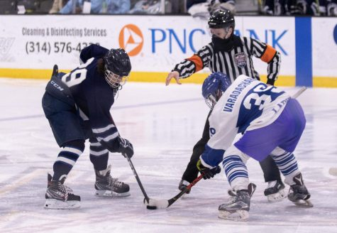 Will Bloomenberg reaches for the puck after the ref drops it.