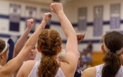 The varsity girls basketball team stands together with their fists raised in the air.