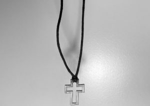 A necklace that bears the religious image of a cross is dangling, ready to drop. Letting go of something that was once so personal is very difficult no matter the circumstances; however, with religion there's a little more. The massive stigma around this act only accentuates these feelings.
