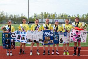 The girls soccer seniors stand with their posters during senior night.