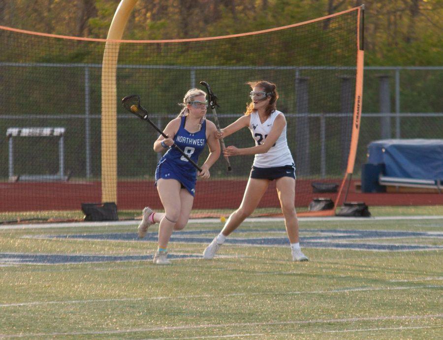 Freshman Sophie Shore defending her opponent from the goal.