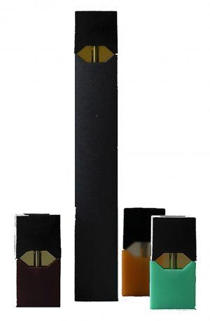A Juul and Juul pods sits still in an open space. A Juul is a vaping device used to intake nicotine filled pods, those pods are known as Juul pods.