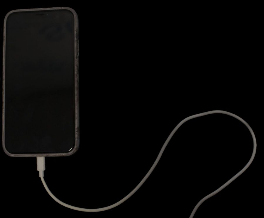 A dead phone sits plugged into a charger. The phone represents mental health, which must stay energized to keep a person from mentally crashing.