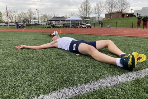 Senior Reed Easterling lays in pain after getting a personal record in the 1600 meter race.