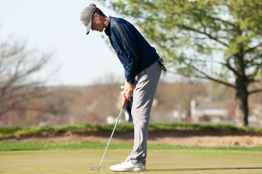 Junior Sam Emrick aligns his club up with the golf ball. He focuses as he prepares to hit the ball.