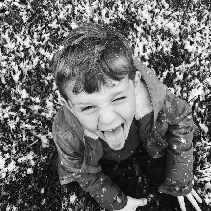 My little brother Eli being goofy in the snow, sitting in the front yard. I like it because of the emotion in his face that shows his personality and the contrast between the white snow and the dark grass as well as in his hair.