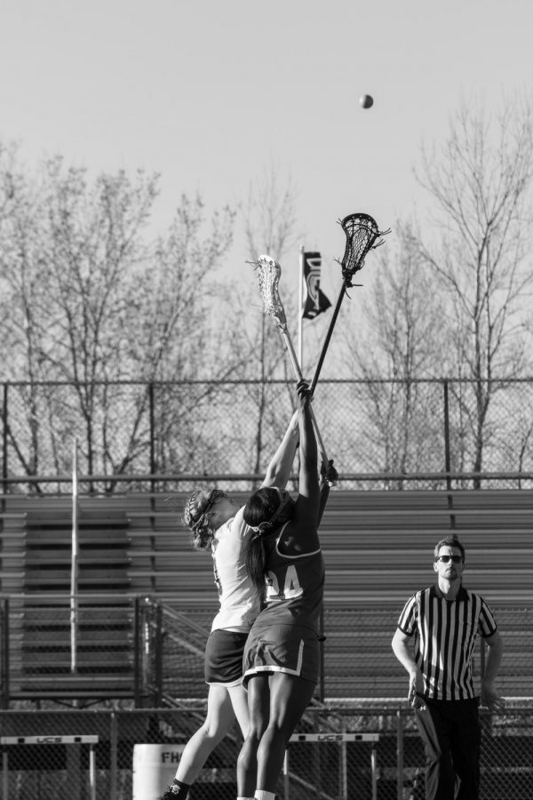 Katelyn Guth taking the draw against Northwest High school at Don Muesch stadium, jumping hoping to receive possession. I like this photo because you can see the ball and their sticks as well as some of the ref.