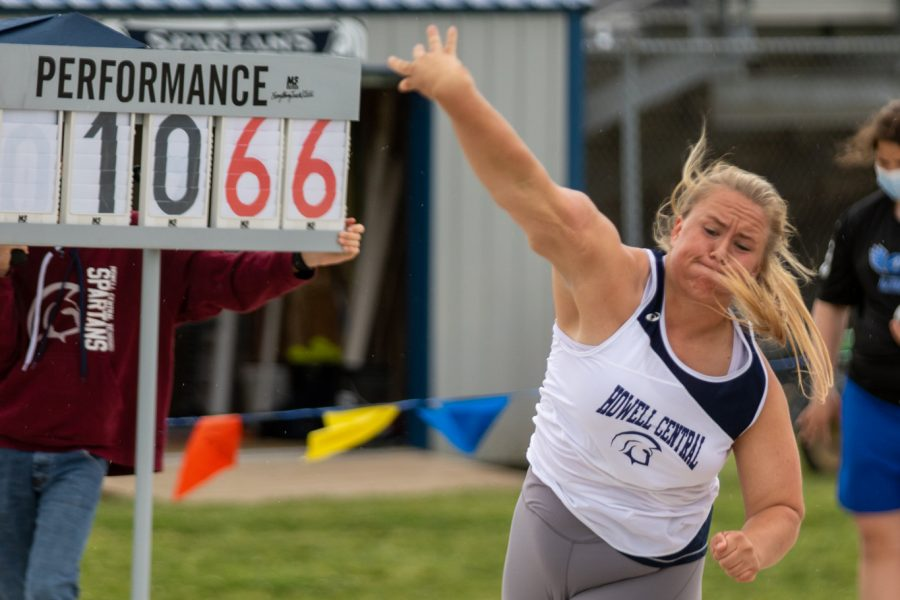 Junior Kennedy Eggering throws for shot put as a fellow track teammate updates the scoreboard.