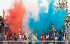 The student section throwing red white and blue powder in the air.
