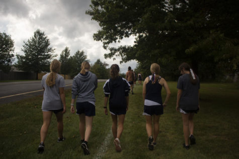 A few JV Girls members walk together behind the rest of the team.