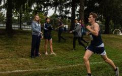 Senior Jack Schriber runs past cheering members of the JV Girls team.