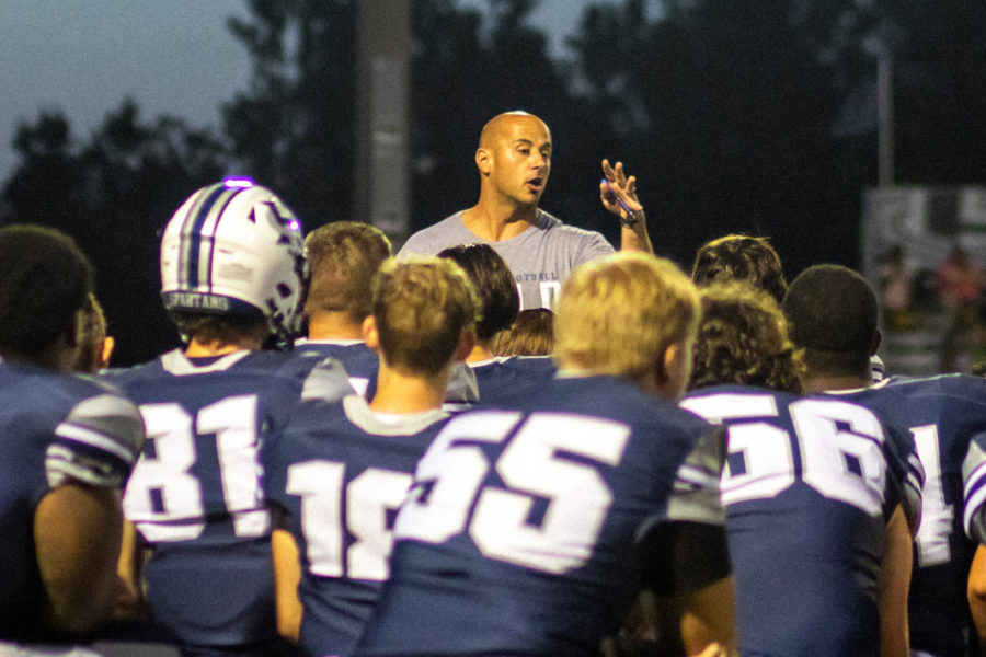 Leading a Team: Speaking to his team after its Aug. 20 jamboree, new head coach Malach Radigan drives home a point to his kneeling players. Coach Radigan's team has gotten off to a 2-4 season as he tries to install his values into the program