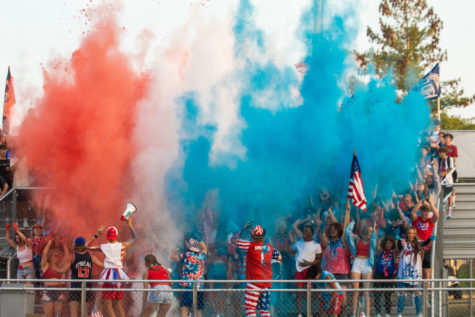 Red, white, and blue powder is thrown up into the air in the student section at the red, white, and blue themed football game. There is a newfound sense of school spirit that shines through in the student section.