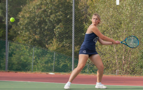 Junior Katie Groat hitting a backhanded shot.