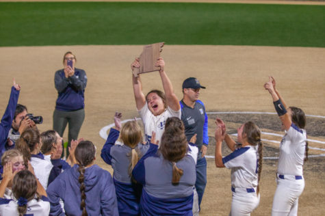 Senior Kennedy Jensen holding up the District Title as the team cheers.