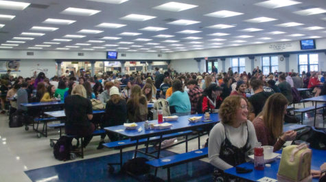 The cafeteria is full of students eating lunch and socializing with one another. The crowdedness of the cafeteria can be overwhelming for some students.