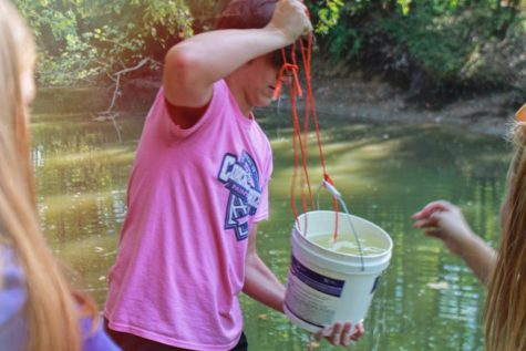 HOSA Vice President Zach Lewis holding a bucket of water from a lake. By testing water around FHC, HOSA is able to determine if there are environmental concerns around the school.